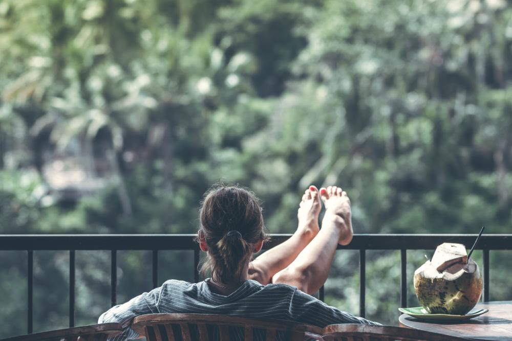 mulher-sentada-em-cadeira-de-madeira-na-varanda